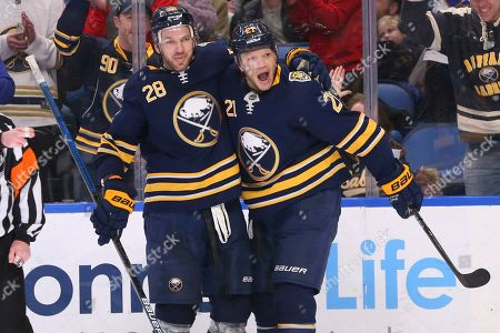 Buffalo Sabres forward Kyle Okposo (21) celebrates his game winning goal with forward Zemgus Girgensons (28) during the third period of an NHL hockey game against the Winnipeg Jets, in Buffalo, N.Y