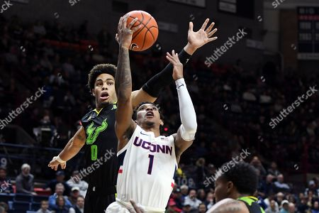 Connecticut's Christian Vital (1) is fouled by South Florida's David Collins (0) during the first half of an NCAA college basketball game, in Storrs, Conn