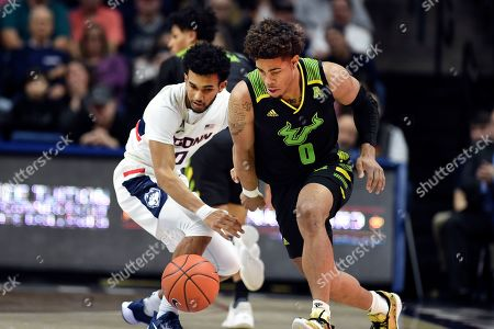Connecticut's Jalen Gaffney (0) and South Florida's David Collins (0) battle for a loose ball during the second half of an NCAA college basketball game, in Storrs, Conn