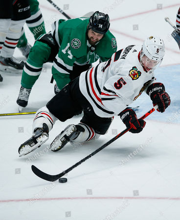 Dallas Stars forward Jamie Benn (14) and Chicago Blackhawks defenseman Connor Murphy (5) battle for the puck during the second period of an NHL hockey game, in Dallas