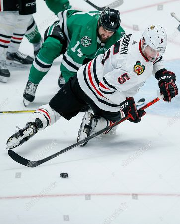 Stock Picture of Dallas Stars forward Jamie Benn (14) and Chicago Blackhawks defenseman Connor Murphy (5) battle for the puck during the second period of an NHL hockey game, in Dallas