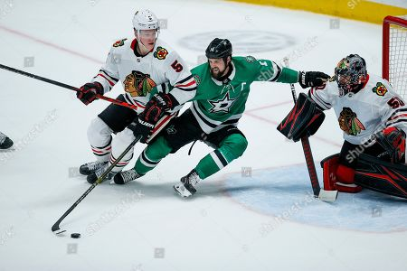 Dallas Stars forward Jamie Benn (14) reaches for the puck as Chicago Blackhawks defenseman Connor Murphy (5) and goaltender Corey Crawford (50) defend during the second period of an NHL hockey game, in Dallas
