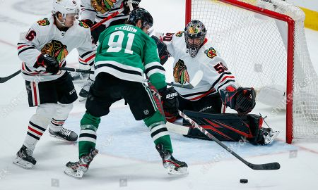 Dallas Stars forward Tyler Seguin (91) attempts a shot as Chicago Blackhawks defenseman Lucas Carlsson (46) and goaltender Corey Crawford (50) defend during the second period of an NHL hockey game, in Dallas. Dallas won 2-1