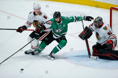 Dallas Stars forward Tyler Seguin (91) reaches for the puck as Chicago Blackhawks defenseman Connor Murphy (5) and goaltender Corey Crawford (50) defend during the second period of an NHL hockey game, in Dallas