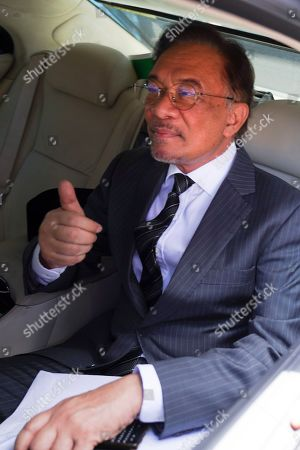 Anwar Ibrahim thumbs up as he leaves his party office in Petaling Jaya, Malaysia,. Malaysia's alliance government under 94-year-old Prime Minister Mahathir Mohamad is threatening to unravel less than two years after a historic election victory ousting the coalition that had ruled the country since independence