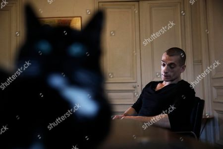 """Controversial Russian political refugee Pyotr Pavlensky speaks during an interview with Associated Press in Paris, . Pavlensky, who seeks attention by staging extreme acts he describes as """"political art,"""" suggested he would release compromising material on other public figures soon, and said he wants all politicians to release their own pornographic films"""