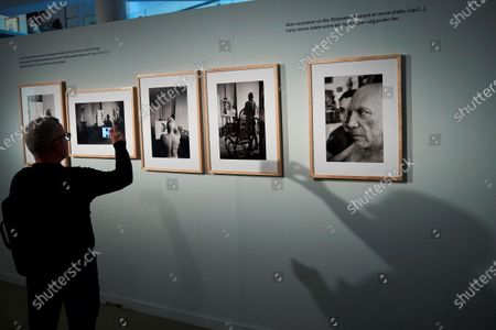 Stock Photo of A man takes smartphone photos of art pieces of the exhibition 'Picasso by Duncan. The knowing look' of 62 pictures taken by US photographer David Douglas Duncan between 1956 and 1962 that shows the private life and work progress of the Spanish painter. The exhibition runs from 22 February to 31 May 2020.