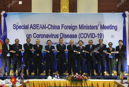 ASEAN Foreign Ministers (L-R) Malaysia's Foreign Minister Saifuddin Abdullah, Myanmar's Union Minister for International Cooperation U Kyaw Tin, Singapore's Foreign Minister Vivian Balakrishnan, Thailand's Minister of Foreign Affairs Don Pramudwinai, Vietnam's Foreign Minister Pham Binh Minh, China's Foreign Minister Wang Yi, Philippines Secretary of Foreign Affairs Teodoro Locsin, Laos Foreign Minister Saleumxay Kommasith, Brunei's Second Minister of Foreign Affairs and Trade Haji Erywan Yusof, Cambodia's Minister of Foreign Affairs Prak Sokhonn, Indonesia's Foreign Minister Retno Marsudi and ASEAN Secretary-General Lim Jock Hoi link their hands during a group photo during the Special ASEAN-China Foreign Ministers' Meeting on Coronavirus Disease or Covid-19 in Vientiane, Laos, 20 February 2020. China's Foreign Minister Wang Yi attended an emergency meeting with his ASEAN counterparts to discuss the cooperation in containing the Covid-19 outbreak crisis.