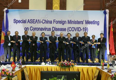 ASEAN Foreign Ministers (L-R) Malaysia's Foreign Minister Saifuddin Abdullah, Myanmar's Union Minister for International Cooperation U Kyaw Tin, Singapore's Foreign Minister Vivian Balakrishnan, Thailand's Minister of Foreign Affairs Don Pramudwinai, Vietnam's Foreign Minister Pham Binh Minh, China's Foreign Minister Wang Yi, Philippines Secretary of Foreign Affairs Teodoro Locsin, Laos Foreign Minister Saleumxay Kommasith, Brunei's Second Minister of Foreign Affairs and Trade Haji Erywan Yusof, Cambodia's Minister of Foreign Affairs Prak Sokhonn, Indonesia's Foreign Minister Retno Marsudi and ASEAN Secretary-General Lim Jock Hoi link their hands for a group photo during the Special ASEAN-China Foreign Ministers' Meeting on Coronavirus Disease or Covid-19 in Vientiane, Laos, 20 February 2020. China's Foreign Minister Wang Yi attended an emergency meeting with his ASEAN counterparts to discuss the cooperation in containing the Covid-19 outbreak crisis.
