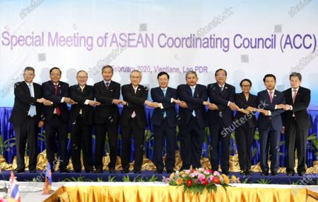 ASEAN Foreign Ministers (L-R) Malaysia's Foreign Minister Saifuddin Abdullah, Myanmar's Union Minister for International Cooperation U Kyaw Tin, Philippines Secretary of Foreign Affairs Teodoro Locsin, Singapore's Foreign Minister Vivian Balakrishnan, Thailand's Minister of Foreign Affairs Don Pramudwinai, Vietnam's Foreign Minister Pham Binh Minh, Brunei's Second Minister of Foreign Affairs and Trade Haji Erywan Yusof, Cambodia's Minister of Foreign Affairs Prak Sokhonn, Indonesia's Foreign Minister Retno Marsudi and ASEAN Secretary-General Lim Jock Hoi lock hands for a group photo during a Special Meeting of ASEAN Coordinating Council (ACC) in Vientiane, Laos, 20 February 2020. China's Foreign Minister Wang Yi attended an emergency meeting with his ASEAN counterparts to discuss the cooperation in containing the Covid-19 outbreak crisis.