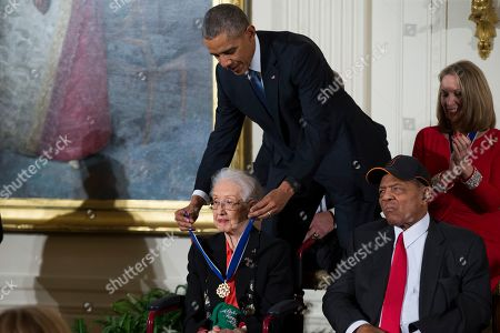 """Barack Obama, Katherine Johnson, Willie Mays. In this Nov. 24, 2015 photo, Willie Mays, right, looks on as President Barack Obama presents the Presidential Medal of Freedom to NASA mathematician Katherine Johnson during a ceremony in the East Room of the White House, in Washington. Johnson, a mathematician on early space missions who was portrayed in film """"Hidden Figures,"""" about pioneering black female aerospace workers, died"""