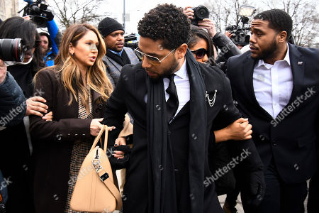 Actor Jussie Smollett, center, departs after an initial court appearance at the Leighton Criminal Courthouse, in Chicago on a new set of charges alleging that he lied to police about being targeted in a racist and homophobic attack in downtown Chicago early last year