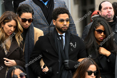 """Former """"Empire"""" actor Jussie Smollett, center, leaves the Leighton Criminal Courthouse in Chicago, after an initial court appearance on a new set of charges alleging that he lied to police about being targeted in a racist and homophobic attack in downtown Chicago early last year"""
