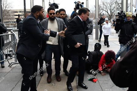 """Former """"Empire"""" actor Jussie Smollett, back center left, arrives for an initial court appearance, at the Leighton Criminal Courthouse in Chicago, on a new set of charges alleging that he lied to police about being targeted in a racist and homophobic attack in downtown Chicago early last year"""