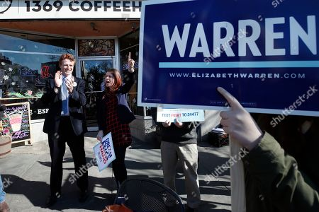 Rep. Joseph P Kennedy III, D-Mass., left, mingles with supporters of Democratic presidential candidate Sen. Elizabeth Warren, D-Mass., in Cambridge, Mass., at a rally to kick off the first morning of early voting in Massachusetts
