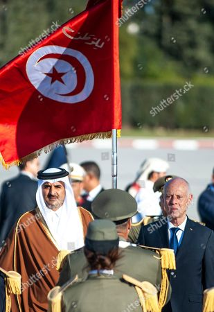 Tunisian President Kais Saied, right, and Emir of Qatar Sheikh Tamim bin Hamad Al Thani review the honour guard upon his arrival in Tunis, Tunisia