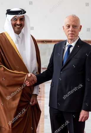 Tunisian President Kais Saied, right, shakes hands with Emir of Qatar Sheikh Tamim bin Hamad Al Thani upon his arrival in Tunis, Tunisia