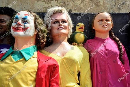 Stock Image of Photograph of the giant dolls that represent the images of the 'Joker' of the US actor Joaquin Phoenix (L), the television personality Ana Maria Braga (C) and the activist Greta Thunberg (R) during a Carnival parade in Olinda , Pernambuco state, Brazil, 24 February 2020. The Swedish activist Greta Thunberg and the Presidents of Brazil, Jair Bolsonaro, and France, Emmanuel Macron, among others were displayed in the traditional parade of giant dolls of the Olinda Carnival. A challenging Greta, four meters high and made of papier-mache, fiberglass, icopor, wood, aluminum, and textiles, led this year the traditional parade 'Apoteose dos Giant Bonecos de Olinda', one of the most massive of the fourth day Carnival in Brazil.