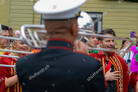 Stock Image of Singer and actor Harry Connick, Jr., listens to the national anthem played by the Marine Corps Marching Band before the Krewe of Orpheus parade during Mardi Gras celebrations in New Orleans
