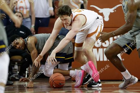 Stock Photo of Taz Sherman, Will Baker. West Virginia guard Taz Sherman, left, and Texas center Will Baker, right, scramble for a loose ball during the second half of an NCAA college basketball game, in Austin, Texas