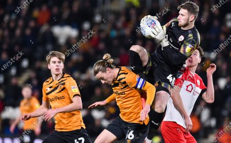 Goalkeeper Bradley Collins of Barnsley claims the ball from Jackson Irvine of Hull City
