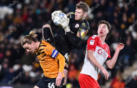 Goalkeeper Bradley Collins of Barnsley claims the ball from Jackson Irvine of Hull City as Aapo Halme looks on