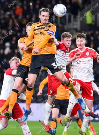 Jackson Irvine of Hull City wins a header against Ben Williams and Aapo Halme of Barnsley