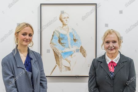 Stock Image of David Hockney's celebrated muse Celia Birtwell (r) and her granddaughter Scarlett Clark with a portrait of Scarlett