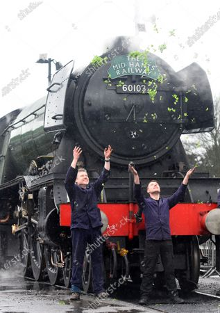Throwing watercress in the air to mark the occasion are crew members Peter Dickson and Jack Johnson celebrate the locomotive's birthday today.