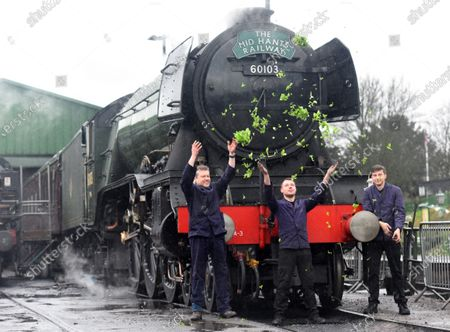 Throwing watercress in the air to mark the occasion are crew members Peter Dickson, Jack Johnson and Ben Chapman celebrate the locomotive's birthday today.