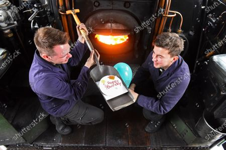 Stock Image of With a cake are crew members Jack Johnson and Ben Chapman to celebrate the locomotive's birthday today.
