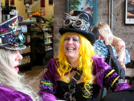 Leslie Ford, left, of Tyler, Texas, and Nicole Hernandez of New Orleans fuel up for Mardi Gras with coffee and croissants at a coffee shop in the French Quarter on . Their first planned stop was the Bourbon Street Awards drag queen and LGBTQ costume contest