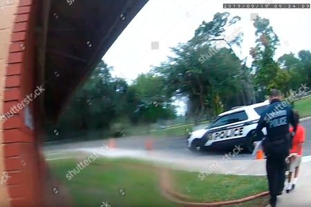 In this image taken from, Orlando Police Department body camera video footage, Orlando Police Officer Dennis Turner leads 6-year-old Kaia Rolle away after her arrest for kicking and punching staff members at the Lucious & Emma Nixon Academy Charter School in Orlando, Fla. Turner was fired shortly after the arrest for not getting the approval of a watch commander to arrest someone younger than 12