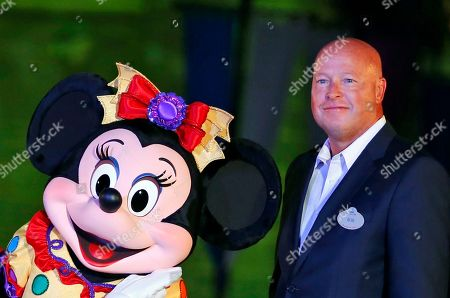 Chairman of Walt Disney Parks and Resorts Bob Chapek poses with Minnie Mouse during a ceremony at the Hong Kong Disneyland, as they celebrate the Hong Kong Disneyland's 10th anniversary. The Walt Disney Co. has named Bob Chapek CEO, replacing Bob Iger, effective immediately, the company announced
