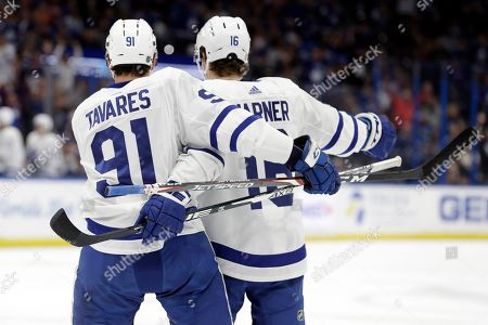Toronto Maple Leafs center John Tavares (91) celebrates his goal against the Tampa Bay Lightning with right wing Mitchell Marner (16) during the first period of an NHL hockey game, in Tampa, Fla