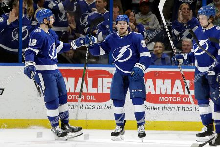 Tampa Bay Lightning center Yanni Gourde, center, celebrates with center Barclay Goodrow, left, and defenseman Mikhail Sergachev, right, after scoring against the Toronto Maple Leafs during the third period of an NHL hockey game, in Tampa, Fla