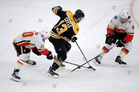 Calgary Flames defenseman Rasmus Andersson (4) and center Derek Ryan (10) strip the puck from Boston Bruins center Charlie Coyle (13) during the first period of an NHL hockey game in Boston