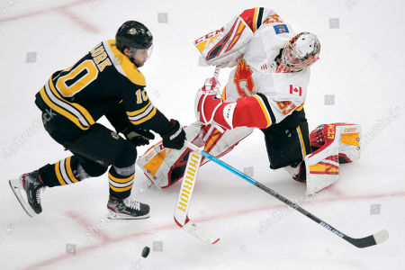 Calgary Flames goaltender David Rittich, right, knocks the puck away from Boston Bruins left wing Anders Bjork (10) during the third period of an NHL hockey game in Boston