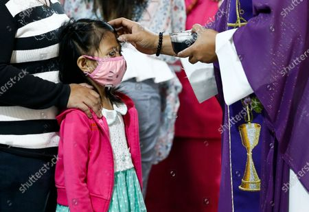 A child wearing a protective mask receives an ash marking on the forehead during a mass to mark Ash Wednesday at Saint Peter Parish Church in Quezon City, east of Manila, Philippines, 26 February 2020. Ash Wednesday marks the beginning of the 40-day Lent period.