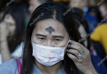 A Filipino with an ash marking on the forehead wears a protective mask after a mass to mark Ash Wednesday at Saint Peter Parish Church in Quezon City, east of Manila, Philippines, 26 February 2020. Ash Wednesday marks the beginning of the 40-day Lent period.