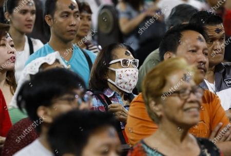 A Filipino (C) with an ash marking on the forehead wears a protective mask during a mass to mark Ash Wednesday at Saint Peter Parish Church in Quezon City, east of Manila, Philippines, 26 February 2020. Ash Wednesday marks the beginning of the 40-day Lent period.