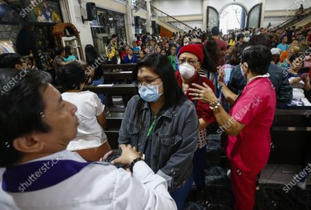 Filipino Catholics wearing protective masks receive ash markings on the forehead during a mass to mark Ash Wednesday at Saint Peter Parish Church in Quezon City, east of Manila, Philippines, 26 February 2020. Ash Wednesday marks the beginning of the 40-day Lent period.
