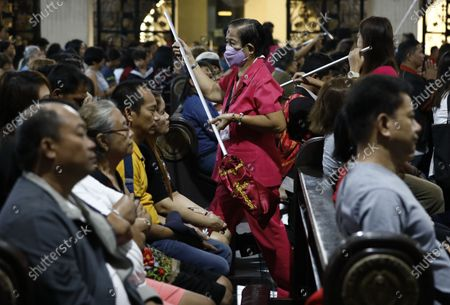 A donation collector (C) wears a protective masks during a mass to mark Ash Wednesday at Saint Peter Parish Church in Quezon City, east of Manila, Philippines, 26 February 2020. Ash Wednesday marks the beginning of the 40-day Lent period.