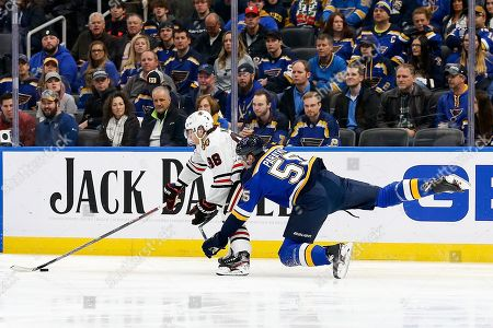 Chicago Blackhawks' Patrick Kane (88) handles the puck in front of St. Louis Blues' Colton Parayko (55) during the first period of an NHL hockey game, in St. Louis