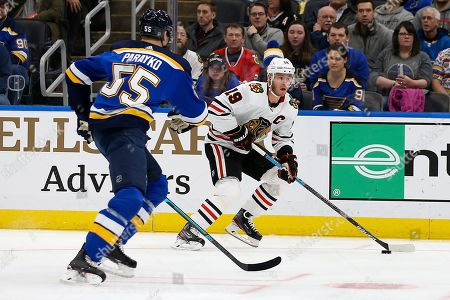 Chicago Blackhawks' Jonathan Toews (19) handless the puck as St. Louis Blues' Colton Parayko (55) defends during the first period of an NHL hockey game, in St. Louis