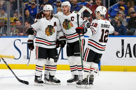 Chicago Blackhawks' Duncan Keith (2), left, is congratulated by teammates Jonathan Toews (19), center, and Alex DeBrincat (12) after scoring a goal during the first period of an NHL hockey game against the St. Louis Blues, in St. Louis