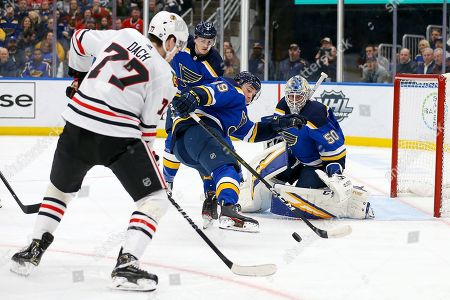 Chicago Blackhawks' Kirby Dach (77) goes after the puck as St. Louis Blues' Vince Dunn (29) and goaltender Jordan Binnington (50) defend the goal during the first period of an NHL hockey game, in St. Louis
