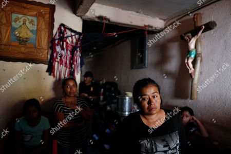 Maria Guadalupe Gallardo Lopez stands with other family members as they mourn her husband Juan Carlos Medina Serrano, in the family's living room, the day his remains were buried, more than two months after armed men pulled him from his home, in Irapuato, Guanajuato state, Mexico. While families like Gallardo López's suffer, many in Guanajuato live lives largely untouched by the violence