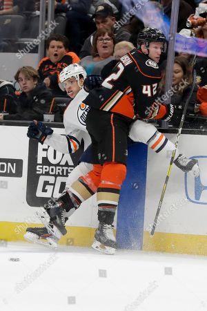 Anaheim Ducks defenseman Josh Manson checks Edmonton Oilers defenseman Caleb Jones during the first period of an NHL hockey game in Anaheim, Calif