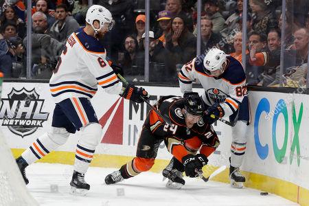 Anaheim Ducks center Carter Rowney goes after the puck between Edmonton Oilers defenseman Adam Larsson, left, and defenseman Caleb Jones during the second period of an NHL hockey game in Anaheim, Calif